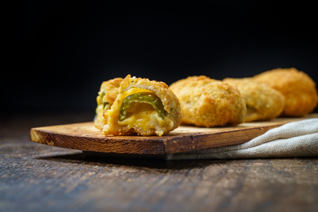 Crispy fried cheddar cheese jalapeno popper bites served on wooden cedar plate with dark moody lighting Фото со стока