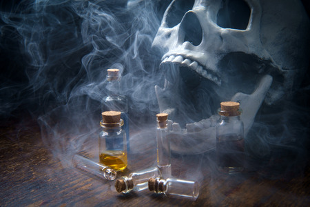 Witches magic potion poison bottles with vapors and human skull Stockfoto