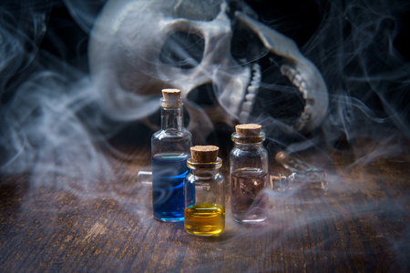 Witches magic potion poison bottles with vapors and human skull 版權商用圖片