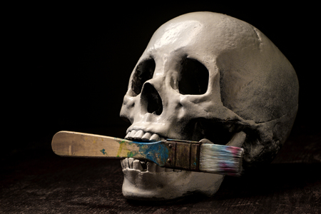 Starving artist human skull eating or holding paintbrush in mouth