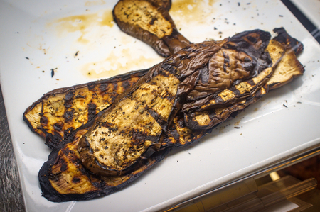 Italian Eggplant grilled with balsamic vineger showing grill lines displayed in glass deli case