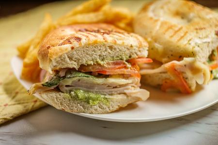 Smoked bistro turkey panini with provolone cheese pesto and tomatoes on focaccia bread Stock Photo