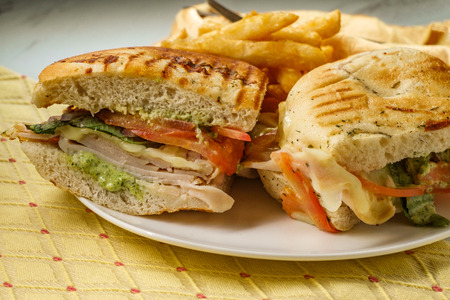 Smoked bistro turkey panini with provolone cheese pesto and tomatoes on focaccia bread