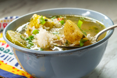 Peruvian cilantro chicken soup or Aguadito de Pollo with yukon gold potatoes corn on the cob and lime slice