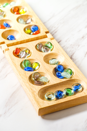 Traditional Mancala boardgame with glass pieces on marble table Stok Fotoğraf