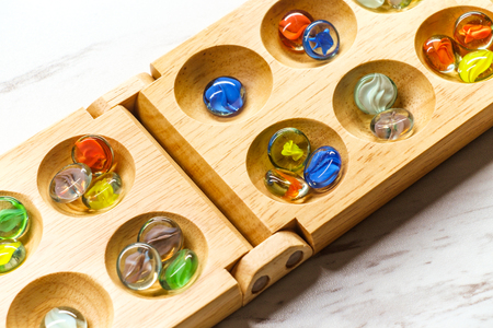 Traditional Mancala boardgame with glass pieces on marble table Stock fotó