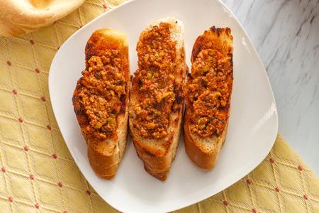 Traditional Portuguese olive bruschetta petiscos appetizer on crusty bread