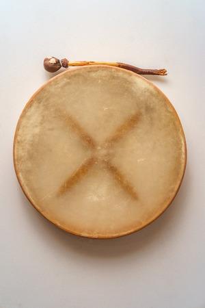 Traditional Irish bodhran drum hung on wall with tipper Фото со стока