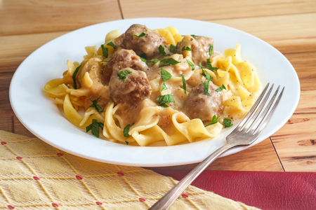 Swedish meatballs in creamy gravy with curly egg noodles and parsley garnish
