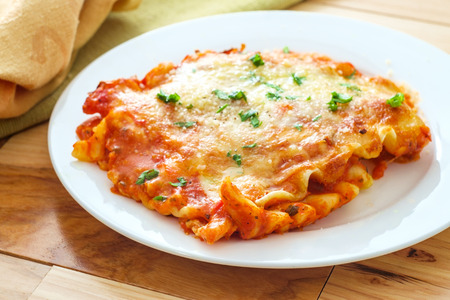 Hausgemachte italienische Käselasagne auf Holzküchentisch