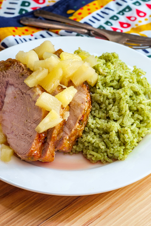Cuban sliced pork roast topped with pineapple tidbits and a side of green rice