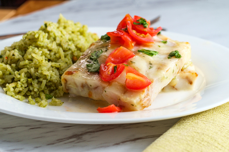 Grilled Alaskan Pollock fish fillets with lemon butter and green rice 免版税图像