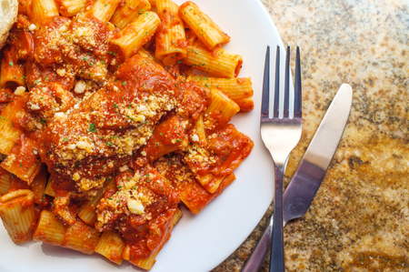 Bolognese braciola with rigatoni and sliced crusty bread 写真素材