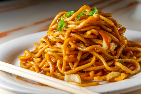 Eating Chinese vegetable lo mein noodles with chopsticks