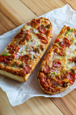 Supreme French bread pizza with pepperoni sausage black olives red onion and green bell pepper toppings