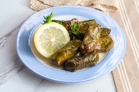 Armenian yaprak dolma, stuffed grape leaves garnished with lemon and fresh parsley