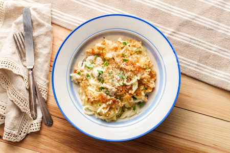 Creamy baked chicken alfredo with spaghetti pasta topped with parmesan and mozzarella cheeses and panko breadcrumbs