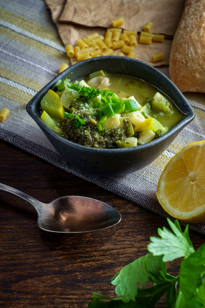 Vegetarian minestrone soup topped with pesto scallions and grated parmesan cheese