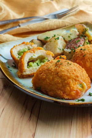 Chicken croquettes stuffed with cheese and broccoli served with roasted garlic herbed red potatoes