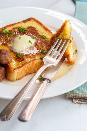 Classic American breakfast french toast with maple syrup served with side of sausage links