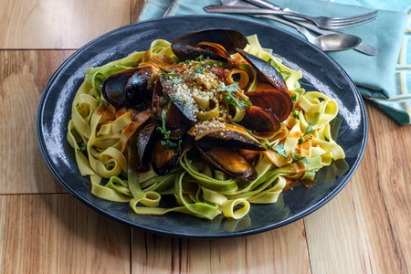 Seafood shell-on mussels marinara Italian seafood dish with tagliatelle pasta