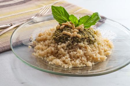 Healthy pesto quinoa salad with basil and pine nut garnish