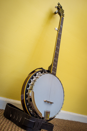 Fancy five string banjo leaning against yellow wall