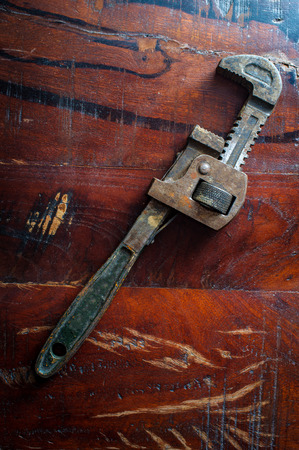 Old rusty adjustable monkey wrench contractors tool on worn wooden floor Stock Photo