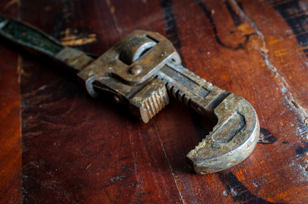 Old rusty adjustable monkey wrench contractors tool on worn wooden floor