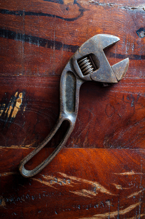 Old rusty adjustable wrench contractors tool on worn wooden floor