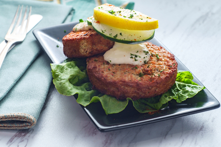 Seasoned crab cakes garnished with romaine lettuce sliced lemon and tartar sauce