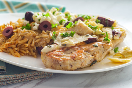 Greek grilled chicken piccata with kalamata olives and artichoke hearts with a side of Mediterranean herbed orzo topped with feta cheese Banque d'images - 123497669