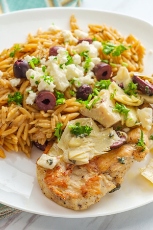 Greek grilled chicken piccata with kalamata olives and artichoke hearts with a side of Mediterranean herbed orzo topped with feta cheese Banque d'images - 123497670