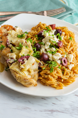 Greek grilled chicken piccata with kalamata olives and artichoke hearts with a side of Mediterranean herbed orzo topped with feta cheese Banque d'images - 123497672
