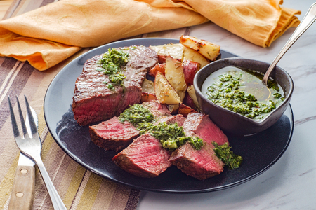 Juicy rare chimichurri verde grilled steak and red potatoes Stok Fotoğraf