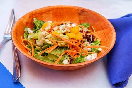 Healthy diet peach salad with crumbled blue cheese in a wooden bowl Stock Photo - 124643041