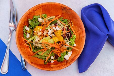 Healthy diet peach salad with crumbled blue cheese in a wooden bowl Stock Photo - 124643044