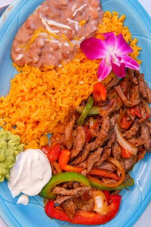 Authentic Mexican cuisine steak fajitas with rice and refried pinto beans