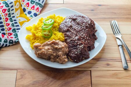 Mexican mole poblano chicken with rice and refried pinto beans Stock Photo