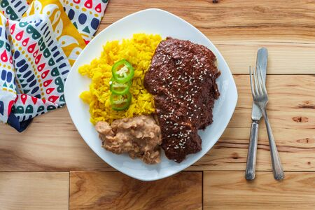 Mexican mole poblano chicken with rice and refried pinto beans Standard-Bild