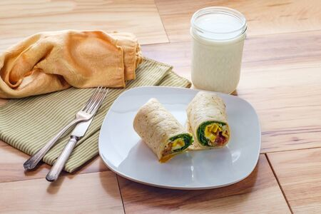 Egg and bacon American breakfast sandwich wrap with a glass of milk