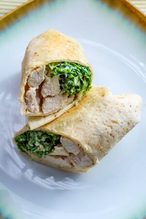 Chicken Caesar salad wrap sandwich with kale and parmesan cheese
