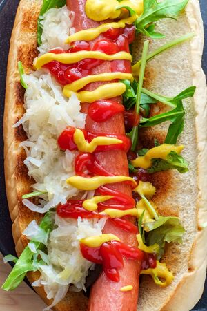Ketchup and mustard on a hot dog with arugula and sauerkraut Stock Photo