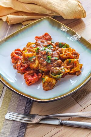 Tortellini Italian ragu alla Bolognese sauce with sausage with basil garnish Stock Photo