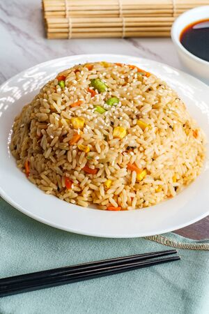 Chinese food vegetable fried rice with chopsticks and soy sauce