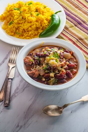 Hot and spicy bowl of Chili con carne served Mexican yellow rice
