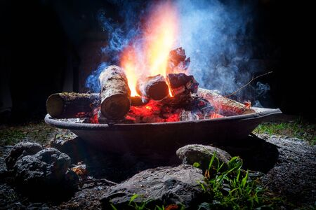 Summer camping fire pit with blue smoke