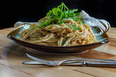 Whole wheat Italian fettuccine alfredo with arugula garnish