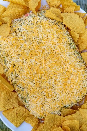 Tortilla chips with 7 layer bean dip for outdoor picnic party appetizer Stock Photo