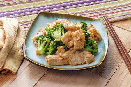 Chinese food chicken and broccoli take out with chopsticks Imagens